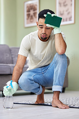 Buy stock photo Shot of a young man taking a break from chores at home