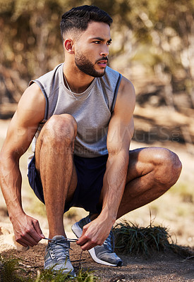 Buy stock photo Full length shot of a handsome young man crouching down to tie his shoelaces before going on an outdoor run