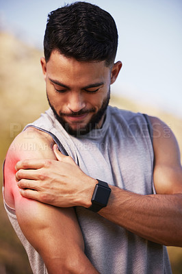 Buy stock photo Shot of a handsome young man standing alone outside and suffering from a sore shoulder during his run