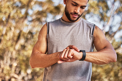 Buy stock photo Shot of a handsome young man standing alone and setting a timer on his watch before running outside