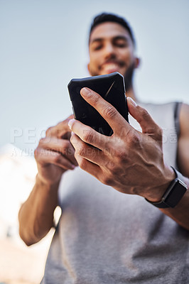 Buy stock photo Shot of a young man standing alone outside and using his cellphone during his run