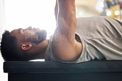 Buy stock photo Shot of a young man working out with a bench press in a gym