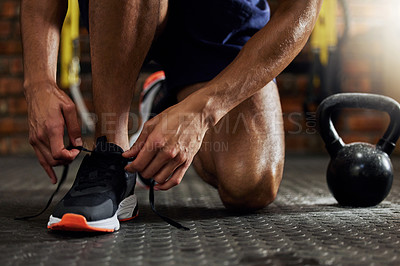 Buy stock photo Shot of an unrecognizable man tying his shoelaces before a workout in the gym