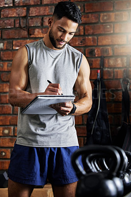Buy stock photo Shot of a young man doing inventory while working in a gym