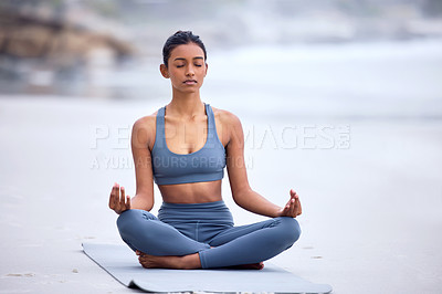 Buy stock photo Full length shot of an attractive young woman meditating while practicing yoga on the beach