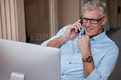 Buy stock photo Shot of a mature businessman sitting alone in the office and using his computer and cellphone