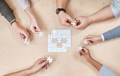Buy stock photo High angle shot of an unrecognizable group of businesspeople huddled together and doing a puzzle in the office