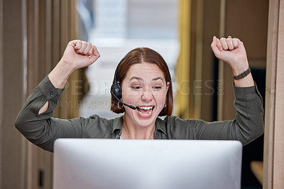 Buy stock photo Shot of a young call centre agent sitting alone in the office and celebrating a success wile using her computer