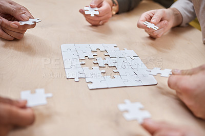 Buy stock photo Cropped shot of an unrecognizable group of businesspeople huddled together and doing a puzzle in the office