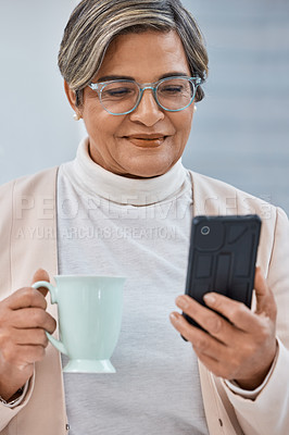 Buy stock photo Shot of a mature businesswoman drinking coffee while using a cellphone in an office