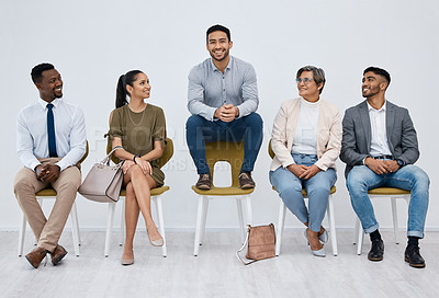 Buy stock photo Studio portrait of a young businessman sitting on a chair alongside candidates against a white background