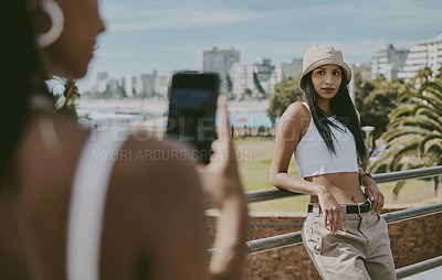 Buy stock photo Shot of a young woman taking pictures of her friend in the city