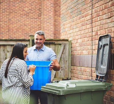 Buy stock photo Shot of a couple emptying their recycling container outside