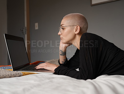 Buy stock photo Shot of a young woman using her laptop while lying on her bed