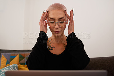 Buy stock photo Shot of a young woman looking stressed while using her laptop at home
