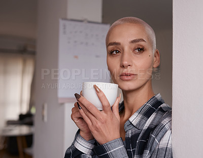 Buy stock photo Shot of a young woman drinking a cup of coffee at home