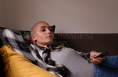 Buy stock photo Shot of a young woman holding a remote control while relaxing on the couch at home