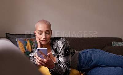 Buy stock photo Shot of a young woman using her cellphone while relaxing on the couch at home