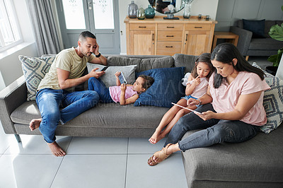Buy stock photo Shot of a young family relaxing at home