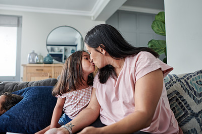 Buy stock photo Shot of a young mother giving her daughter a kiss at home