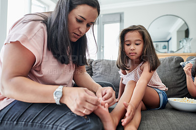 Buy stock photo Shot of a young mother applying a bandaid to her daughter's wound at home