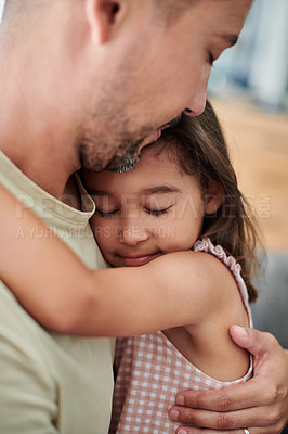 Buy stock photo Shot of a young father holding his sleeping daughter at home