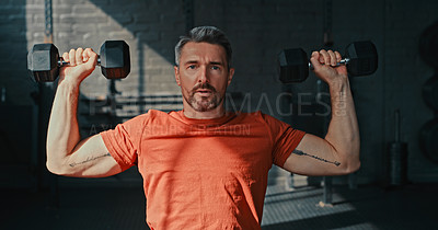 Buy stock photo Shot of a handsome mature man sitting alone and using dumbbells for shoulder press exercises in the gym