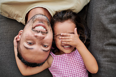 Buy stock photo Aerial shot of a young father and daughter laying on the couch at home