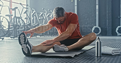Buy stock photo Shot of a handsome mature man sitting and stretching after working out in the gym alone