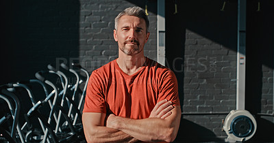 Buy stock photo Shot of a handsome mature man standing with his arms folded after his workout in the gym