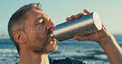 Buy stock photo Shot of a mature man drinking water while exercising along the beach