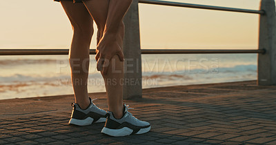 Buy stock photo Closeup shot of an unrecognisable man holding his leg in pain while exercising along the promenade