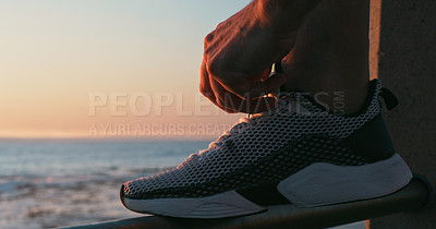 Buy stock photo Closeup shot of an unrecognisable man tying his laces while exercising along the promenade